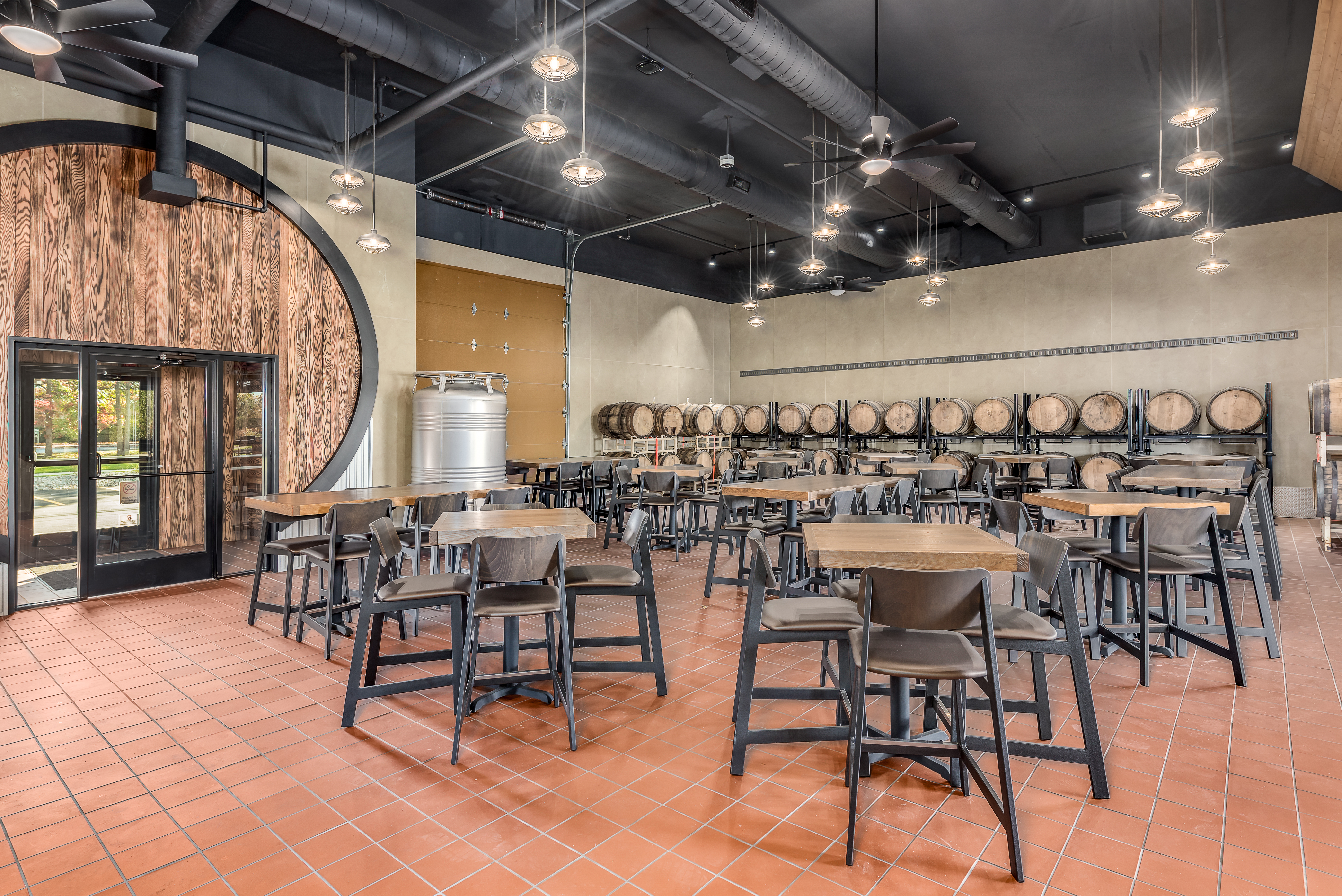 Interior view of the Red Keg Barrel House Event Venue showing the seating accommodations and the equipment used during the barrel aging process.