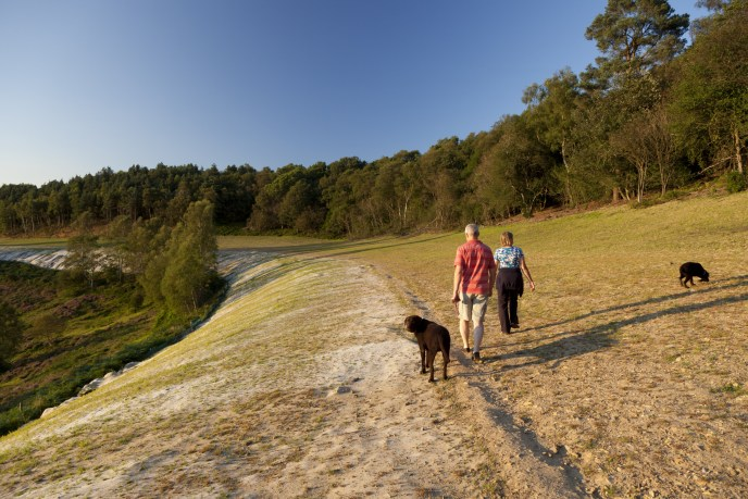 People walking on the old A3 main road, now grassed over, at the Devil's Punch Bowl, Hindhead Common, Surrey.