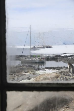 Boats and Penguin through the window at Port Lockroy