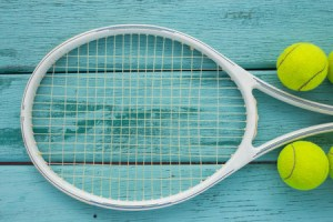 tennis racket with tennis ball on green wood texture