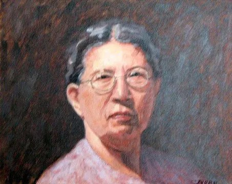 Portrait of an older woman with dark hair and wearing glasses.