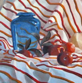 Portrait of red apples and blue glass jar sitting on white cloth with red and orange stripes.