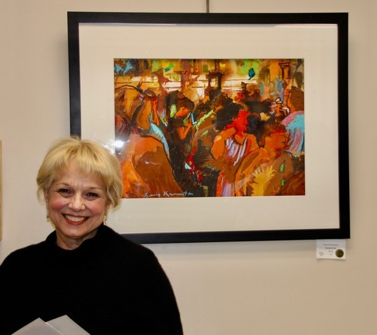 Woman standing next to painting of people at a party.