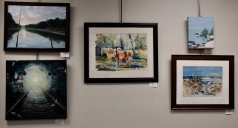 Group of artwork hanging on a wall.