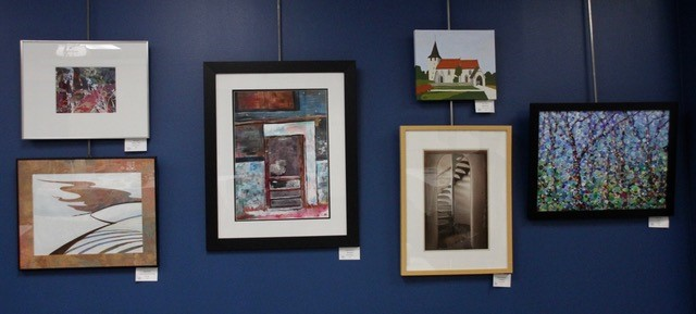 Grouping of artwork hanging on a wall.