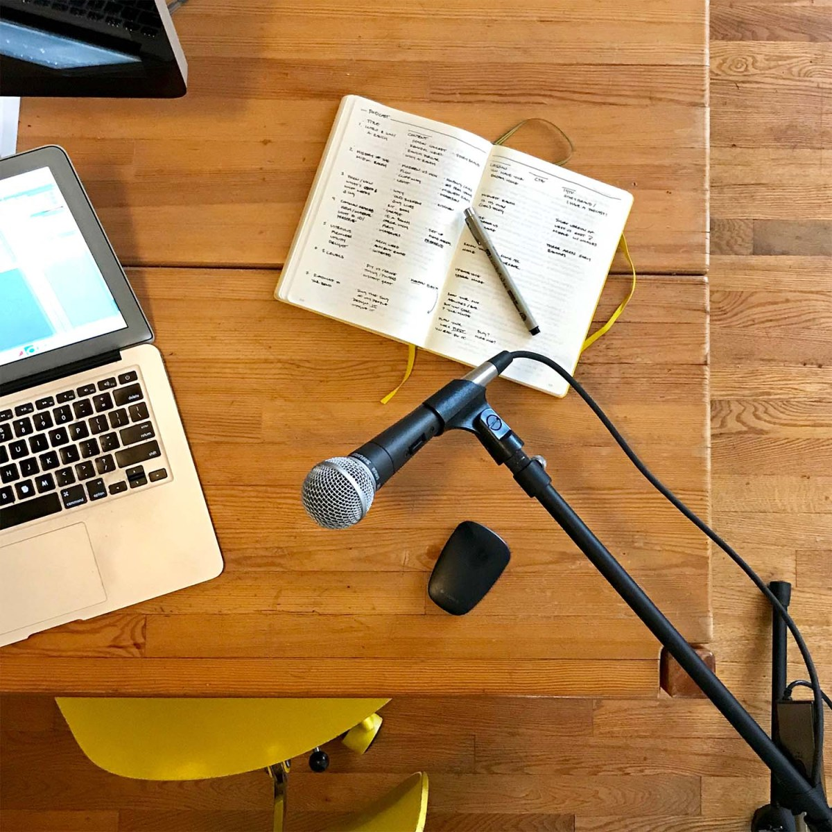 image of desktop with laptop, yellow notebook, mouse and podcasting mic