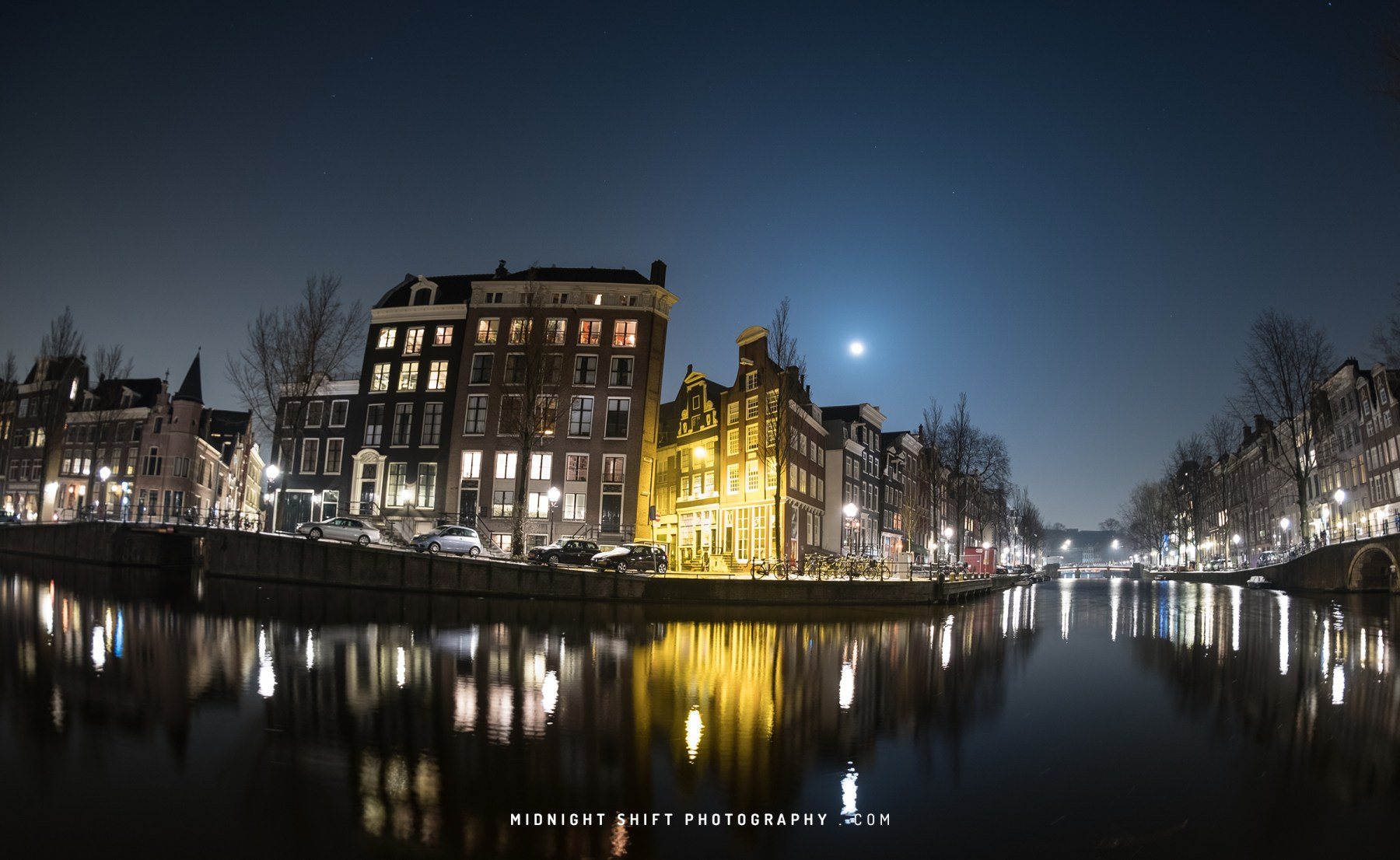 The moon rises over the city of Amsterdam