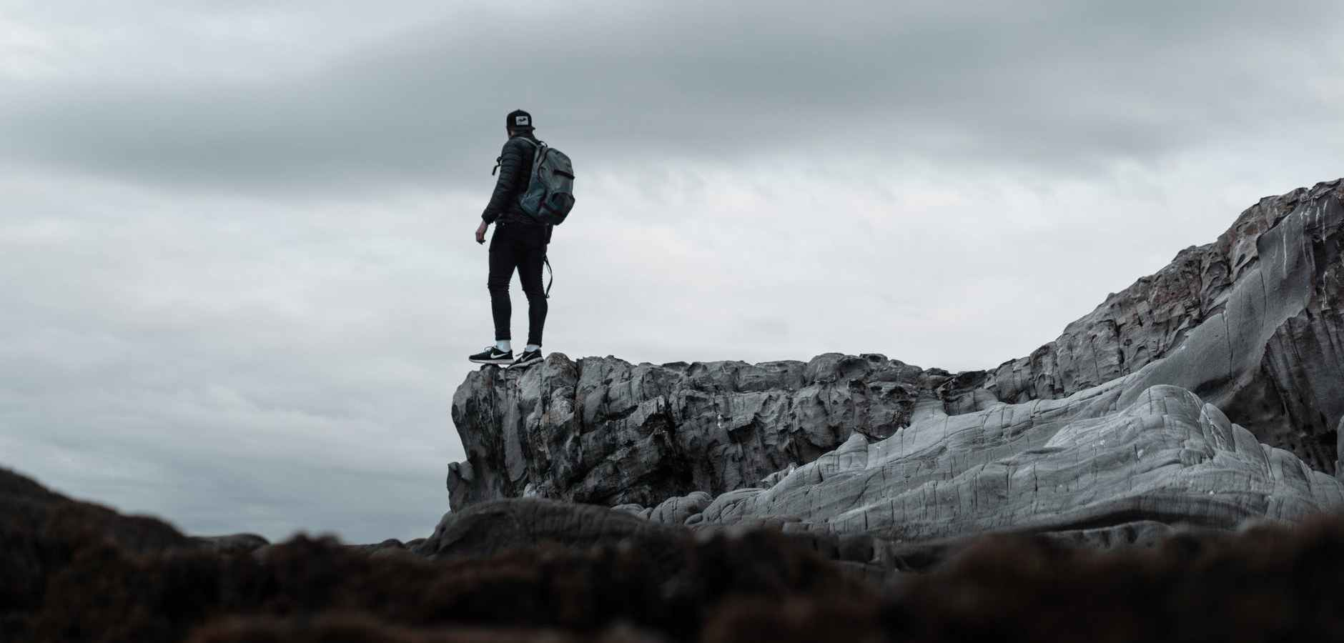 man standing on the end of the rock