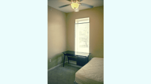 Large bedroom with a ceiling fan in a downtown campus apartment
