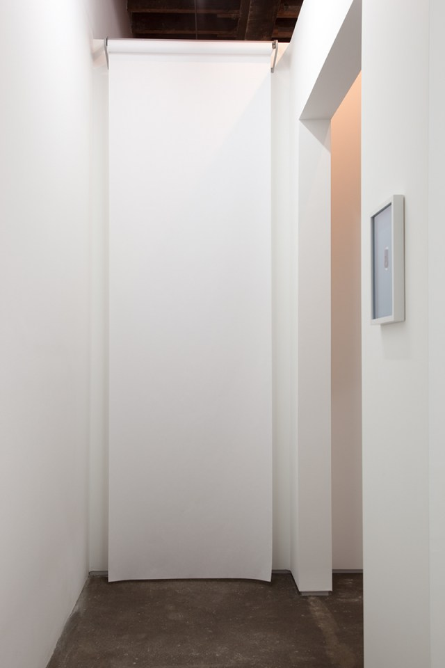 David Catherall, installation view. Left: J|, 2012. Paper roll, steel roll dispenser. 120 x 36 inches. Right: CTHRLL DVD, 2011-2012. Laser cut metal door handle prototype, artist frame. 2 x 1 x ⅛ inches; 10 ¼ x 13 ½ inches framed