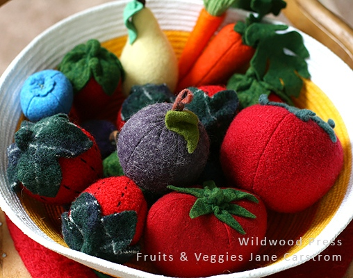 The two strawberries with black stitching are sewn from sweater felt. Boiled wool sweaters aggressively fulled and used as fabric. The other fruits and vegetables are sewn from fulled commercial wool felt. All are stuffed with wool batt.