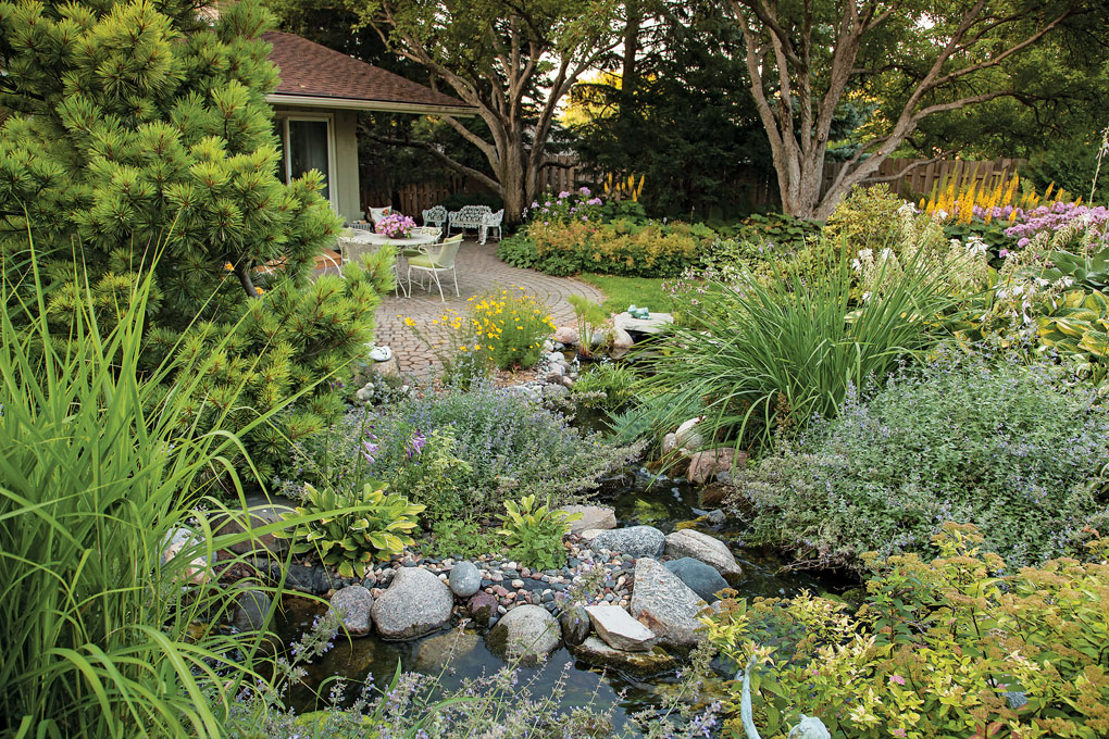 A beautiful, green garden that features a variety of plants and colored flowers set next to a small pond and brick patio.
