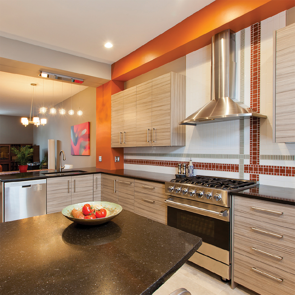 A kitchen with stainless steel appliances, island with fruit bowl perched atop, and splashes of tangerine color by Sawhill Custom Kitchens, a winner in the National Kitchen and Bath Association Minnesota Design Awards.