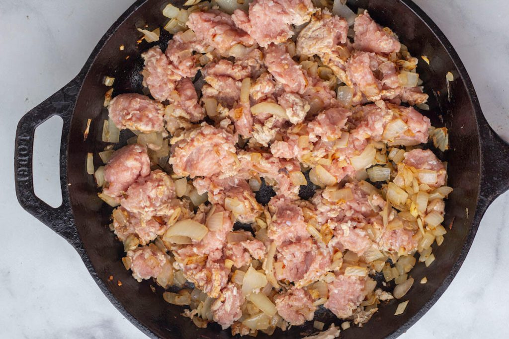 Ground turkey being cooked with sauteed onions and garlic in a cast iron skillet.
