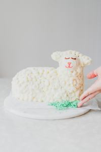 Dyed coconut is sprinkle around the base of a lamb cake.