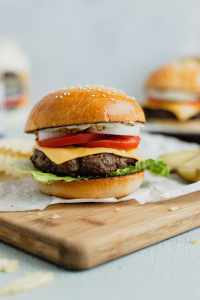 A venison burger with cheese on a brioche bun sits on a piece of parchment paper on a wooden cutting board