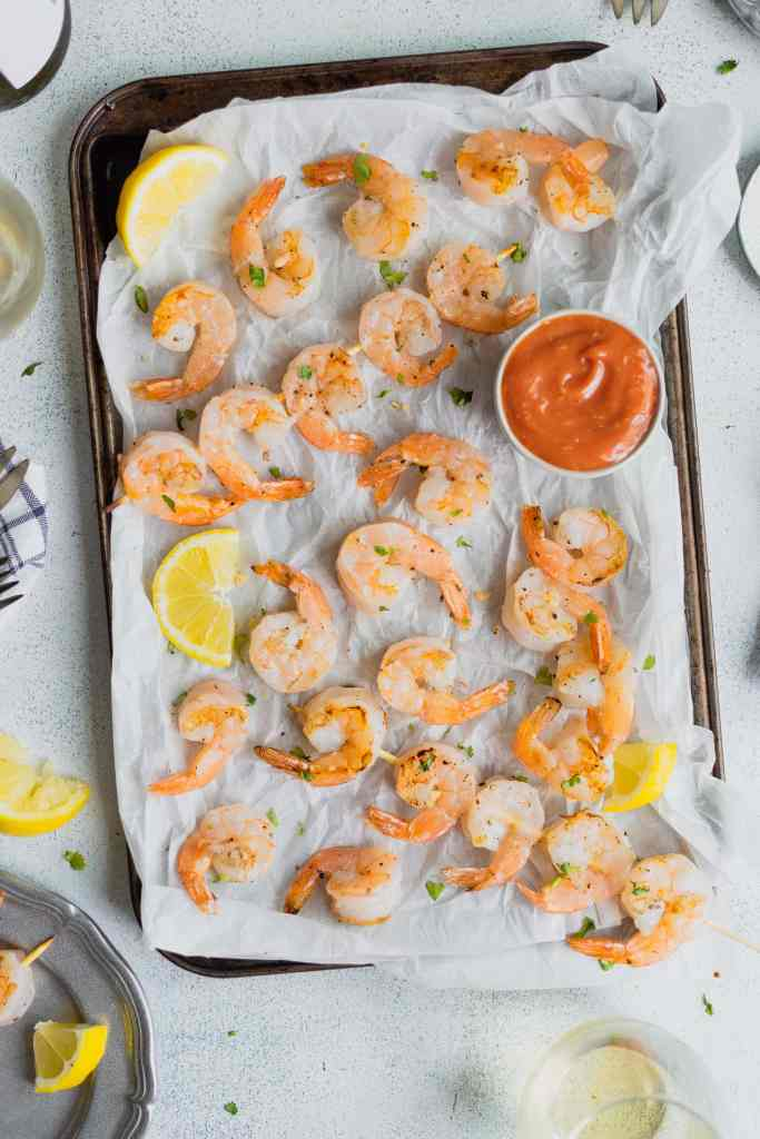 A baking tray covered in parchment paper holds grilled shrimp and a bowl of cocktail sauce.