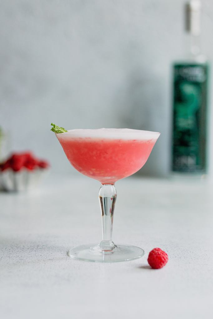 A raspberry gin fizz cocktail is in a vintage coupe glass. Garnished with a mint leaf, a raspberry rests beside the glass on a grey background.