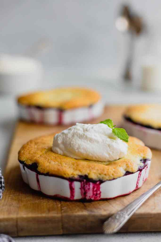 A shallow white ramekin filled with cooked mulberry cobbler sits on a wooden cutting board. There are drips of berry juice down the sides and a dollop of fresh whipped cream on top.