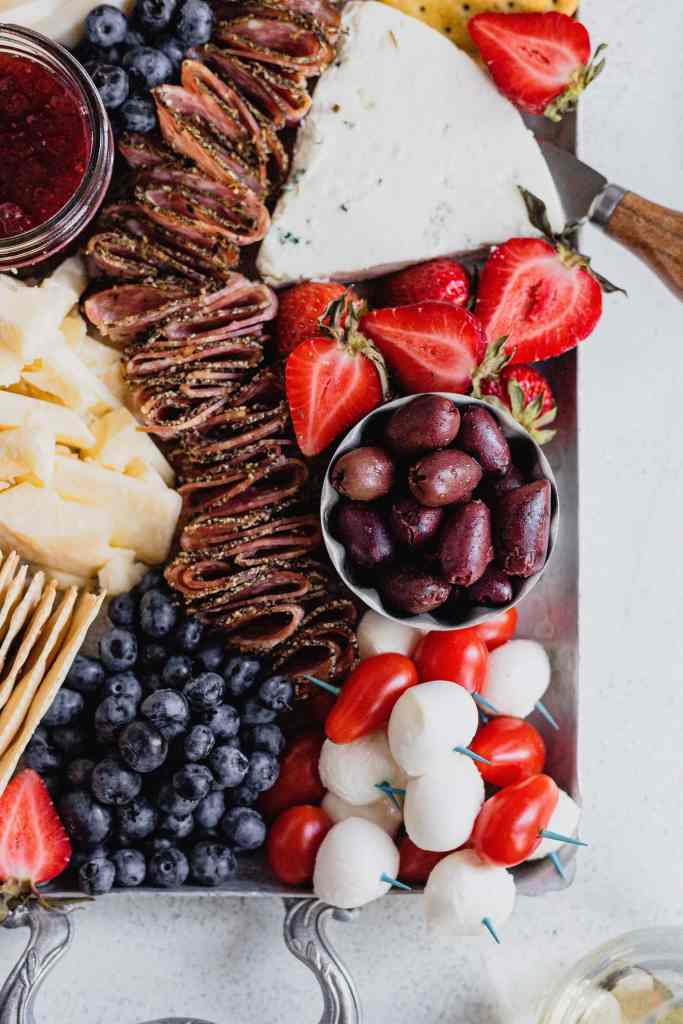 A small silver bowl full of Kalamata olives sits on a silver tray that holds a variety of red, white, and blue snacks for a patriotic cheese tray.