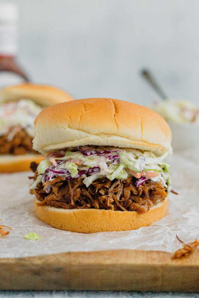 A pulled pork sandwich topped with coleslaw sits on a piece of parchment paper on a wooden cutting board.