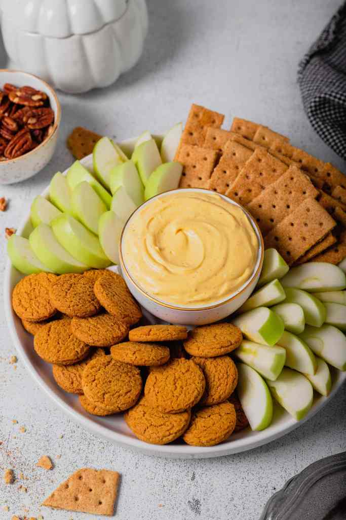A tray filled with cookies, crackers, and apple slices surround a small bowl of pumpkin pie cheesecake dip all on a white background.