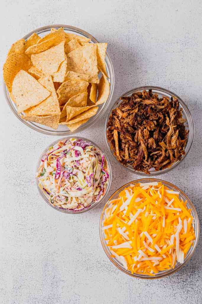 Four glass bowls hold the ingredients for homemade nachos. One bowl has tortilla chips, one has shredded pork, one has shredded cheese, and one has coleslaw.
