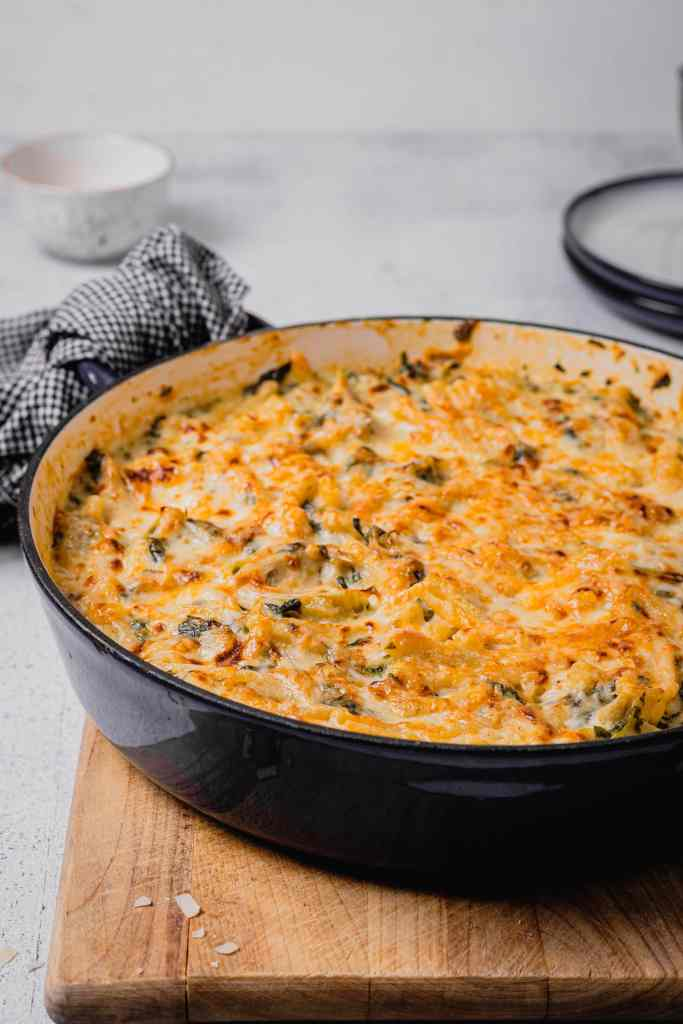 A portrait shot of a large, shallow Dutch oven is filled with Spinach Artichoke Mac and Cheese. The pan is on a wooden cutting board and has a checkered towel tied to a handle. There are two plates and a speckled white bowl in the background.