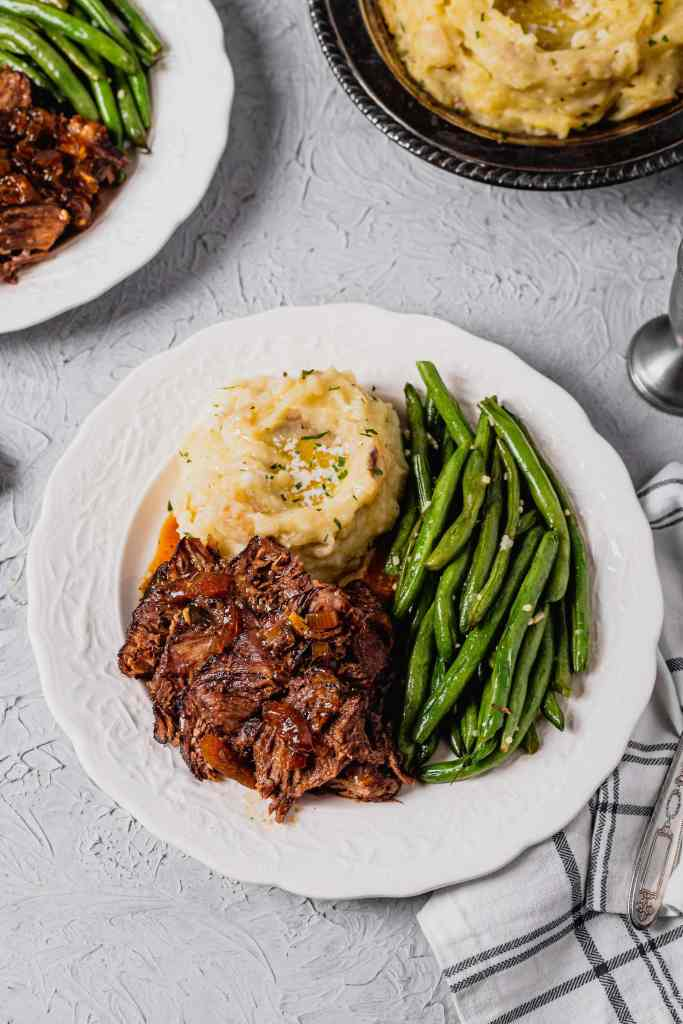 An overhead shot of a white plate filled with beer braised beef roast, buttery mashed potatoes, and sautéed green beans. The beef is covered in a pan sauce. There is a white and blue checkered napkin next to the plate.
