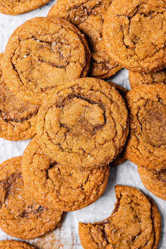 A stack of soft and chewy molasses cookies on a piece of parchment paper. There is a bite taken out of the bottom right cookie.