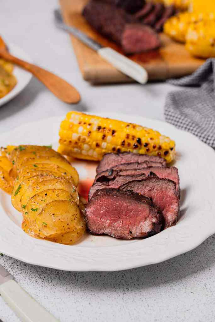 Slices of grilled venison are on a white plate with grilled corn on the cob and grilled potatoes.