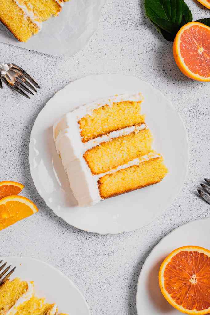 An overhead shot of a three-layer orange cream cake on a white plate. There are forks, other cake slices, and fresh oranges around the plate.