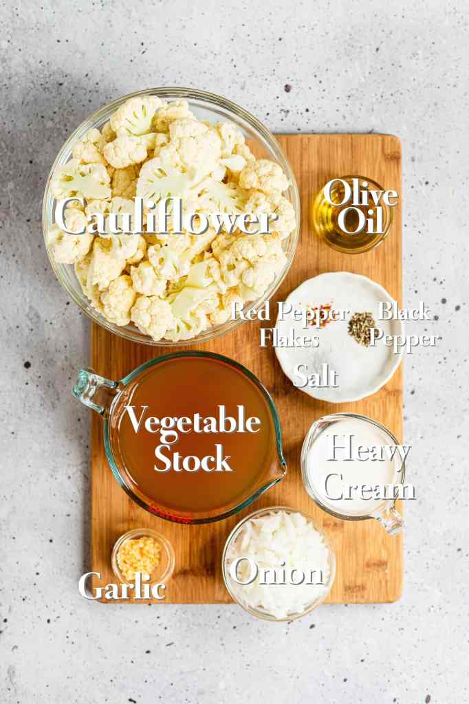 All the ingredients for roasted cauliflower soup sit in glass bowls on a wooden cutting board.