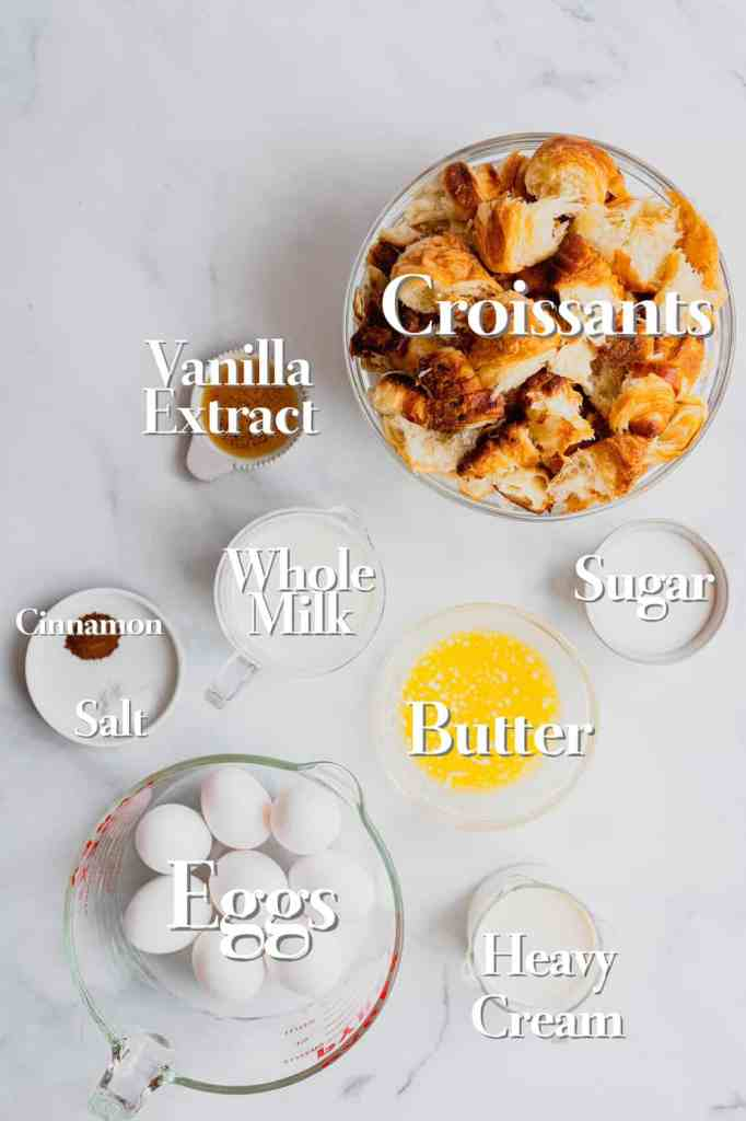 All the ingredients for a croissant French toast bake are in varying sized glass bowls and measuring cups on a white marble back drop.