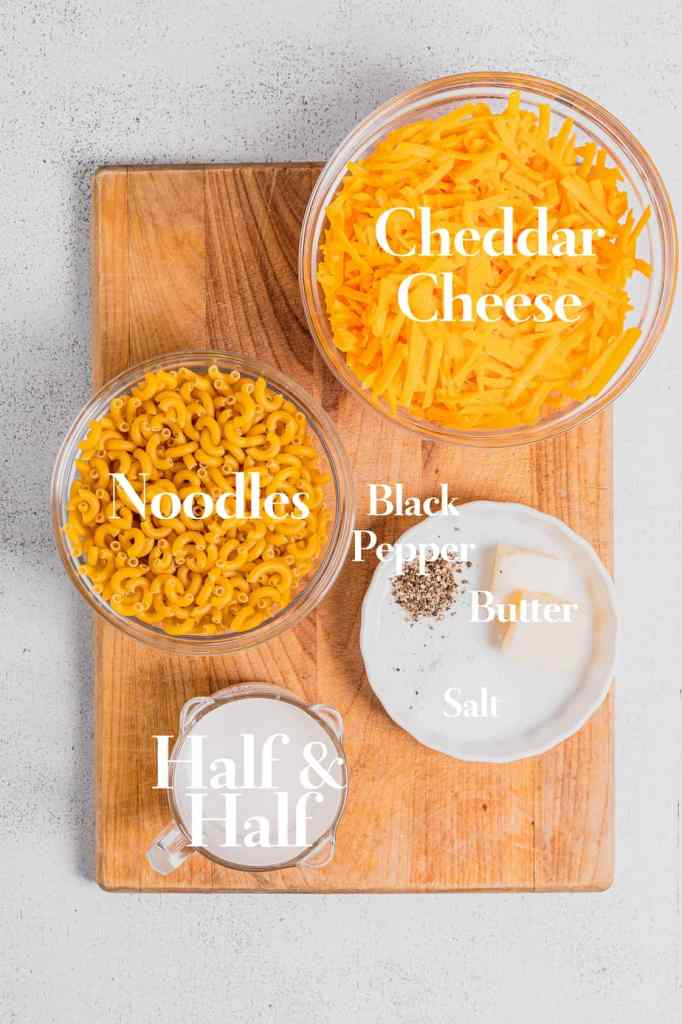 A wooden cutting board filled with the ingredients for this stovetop mac and cheese recipe.