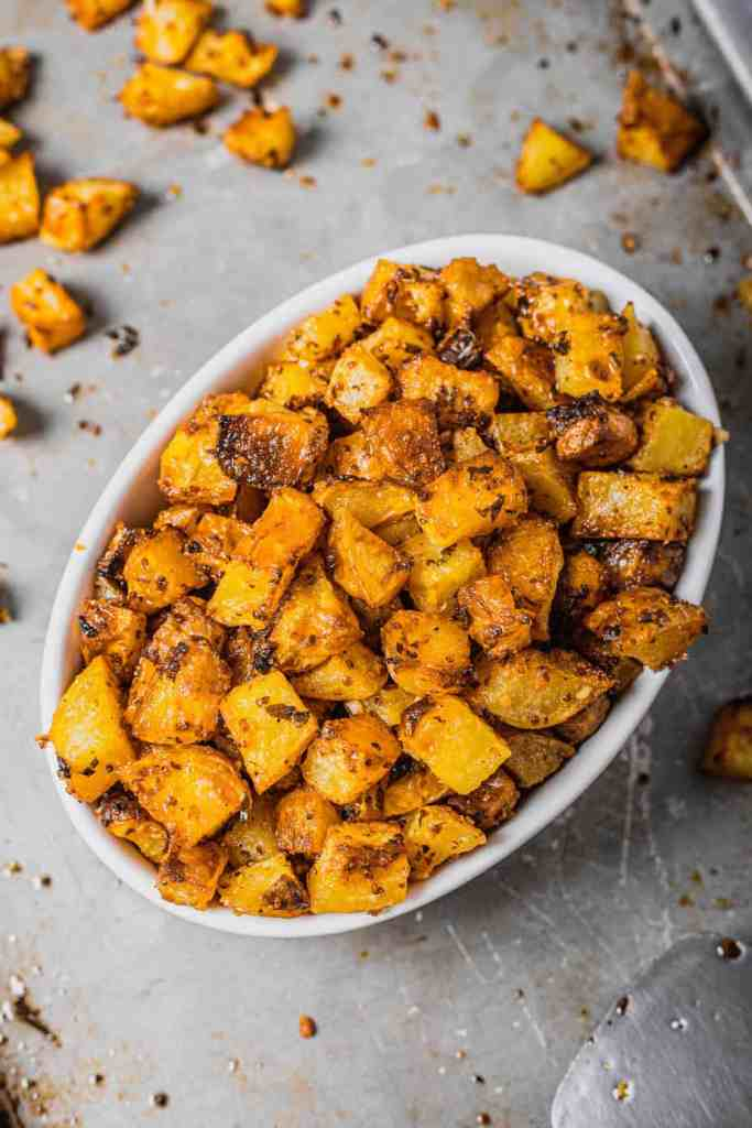A white oval serving dish is filled with oven roasted potatoes with rosemary and mustard on a silver baking tray.