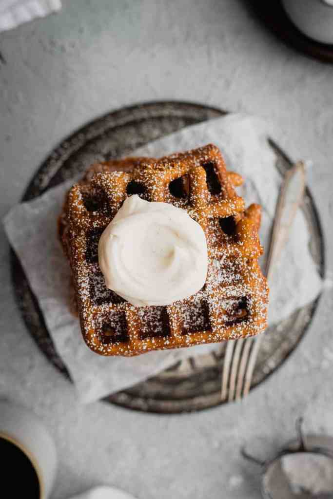 An overhead shot of a stack of gingerbread waffles are set on an overturned antique pie plate on a piece of parchment paper. They are topped with fresh whipped cream. There is a fork next to the waffles and a white pitcher and clear glasses in the background.