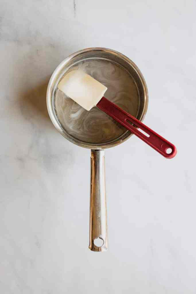 A small saucepot full of peppermint simple syrup with a rubber spatula in it.