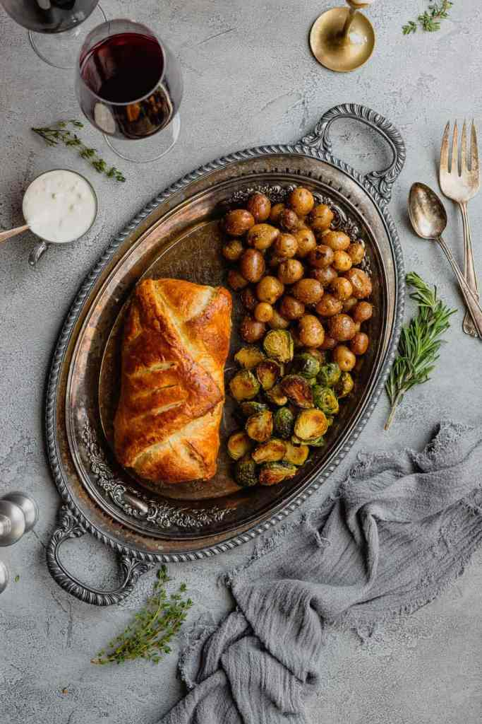 An overhead shot of a silver tray filled with venison wellington wrapped in puff pastry and a pile of roasted potatoes and halved, roasted brussels sprouts.
