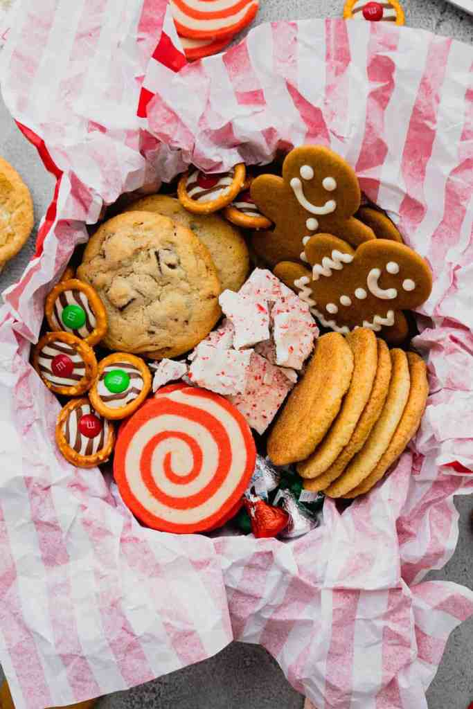 A festive Christmas cookie tin filled with four different kinds of cookies and three types of chocolate candies.