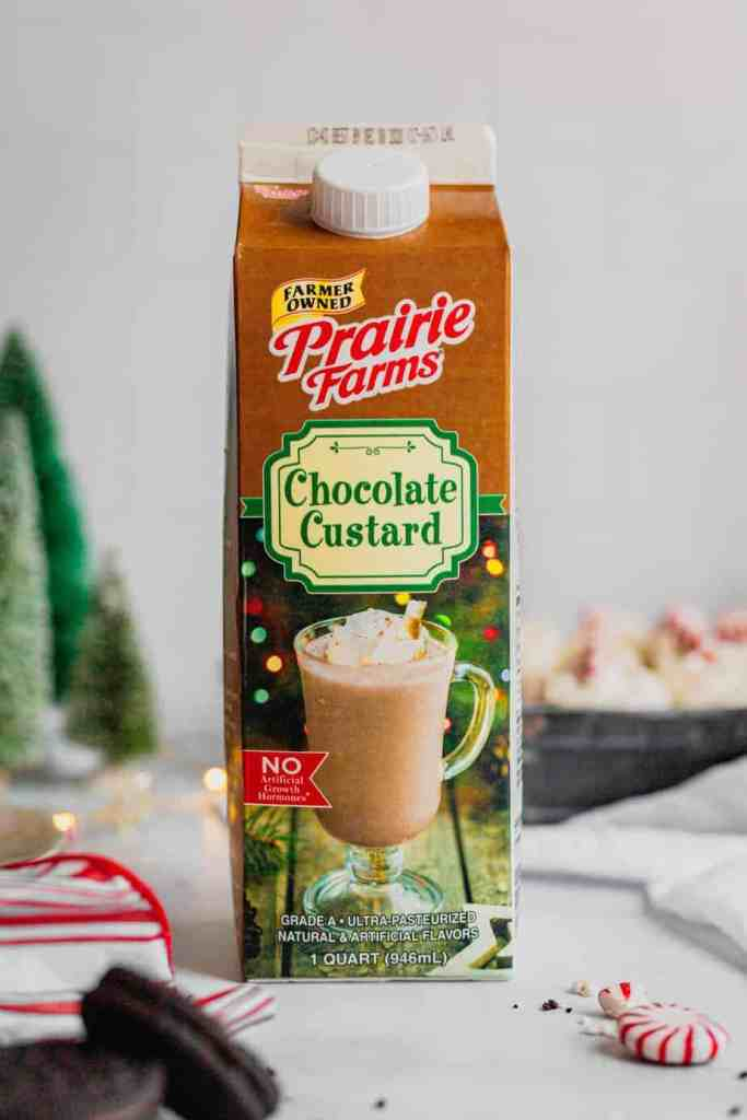 A carton of Prairie Farms Chocolate Custard sits on a counter with a chocolate cream pie int he background and peppermint candies and chocolate cookies in the foreground.