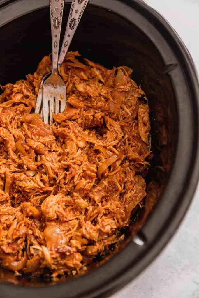 A slow cooker is filled with shredded bbq chicken.