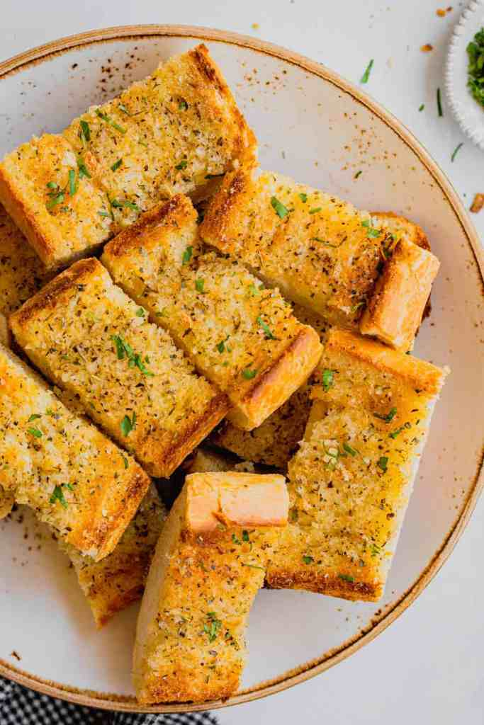A shallow bowl is filled with slices of homemade garlic bread and sprinkled with parsley.