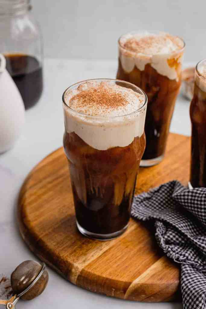 A glass of Irish Cream Cold Foam Cold brew coffee on a wooden serving board.