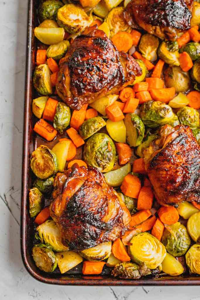 Perfectly roasted chicken thighs are set on top of roasted vegetables on a rimmed sheet tray.