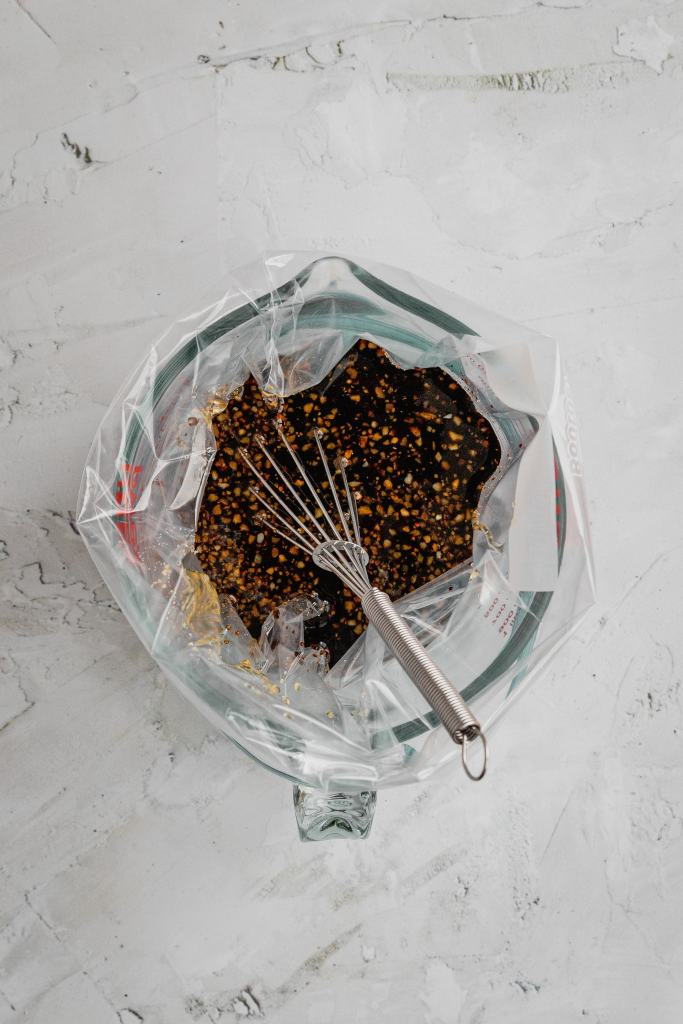 A zip-top bag in a measuring cup full of a honey balsamic marinade.