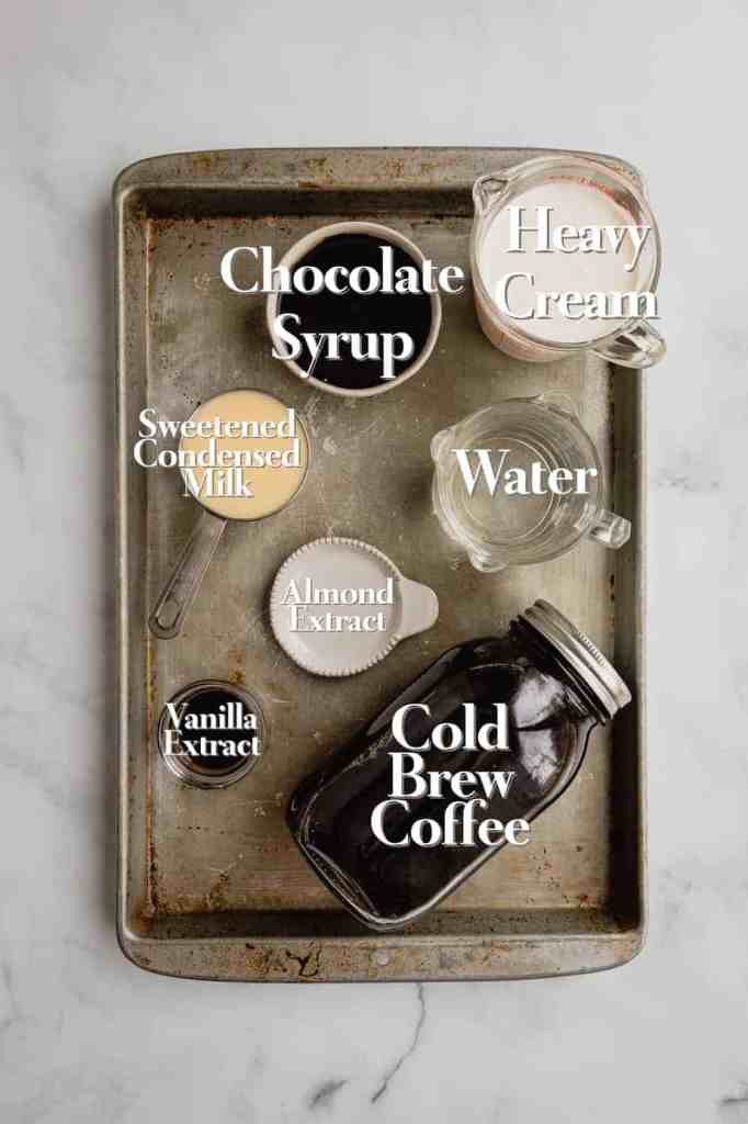 All of the ingredients for Irish Cream Cold Foam are in various bowls and measuring cups on a silvery baking tray.