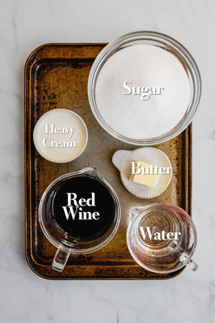 All the ingredients for red wine caramel sauce are in various glass bowls and measuring cups on a baking sheet.