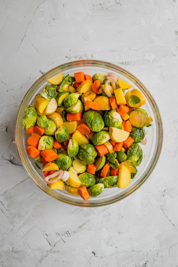 A glass bowl filled with a mixture of fresh vegetables.
