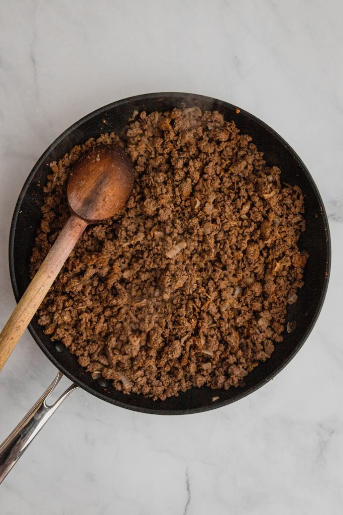 Browned ground venison in a skillet.